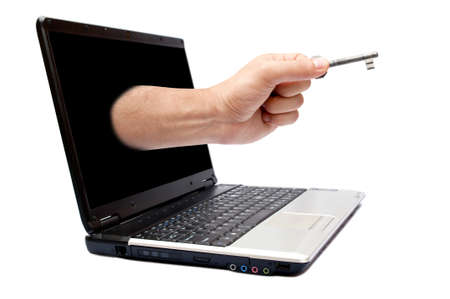 Male hand holding key and coming from laptop screen photo
