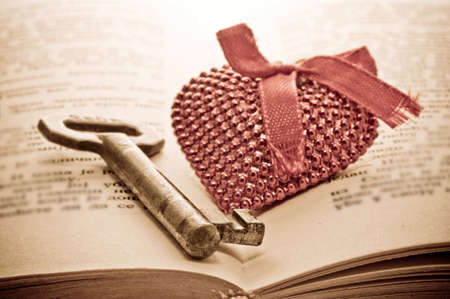 key words  art: Key and heart on the open book - lesson of seduction Stock Photo