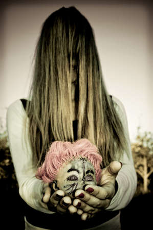 severed: Girl with hair over face holding a severed head doll