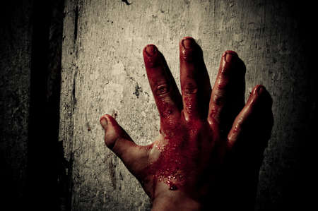 Male bloody hand on the wooden background photo