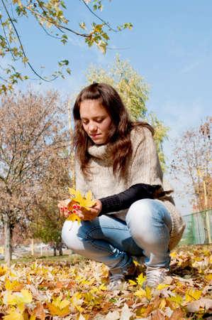 en cuclillas: Adolescente en el parque con las hojas amarillas ca�das de todo