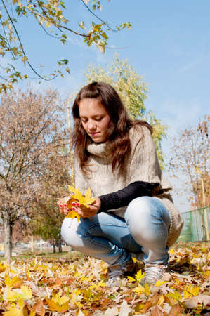 Teenage girl in the park with fallen yellow leaves around photo