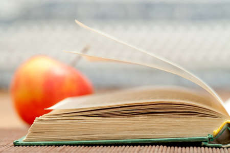 Open book and blurred apple Stock Photo - 11721021