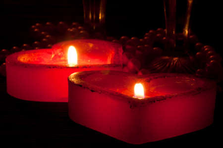 Two heart-shape burning candles, pearls and glasses photo