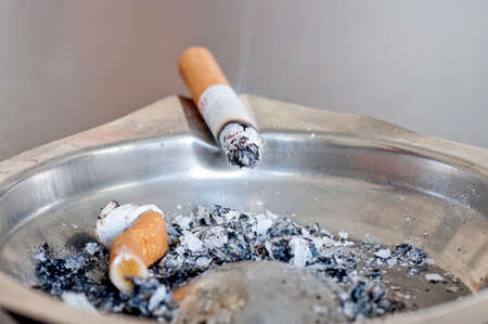 quenched: Cigar on the astray with ash and one quenched cigar Stock Photo