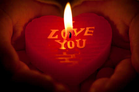 Burning heart-shape candle in female hands photo