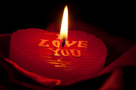 Burning heart candle on the red satin in the dark photo