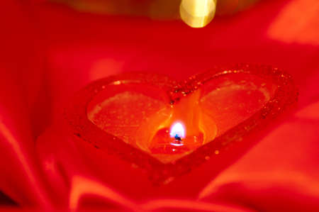 Burning heart-shape candle on the red satin photo