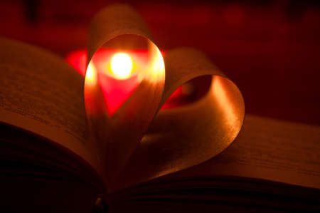 Close-up of book pages folded into a heart shape and burning heart-shape candle through him photo