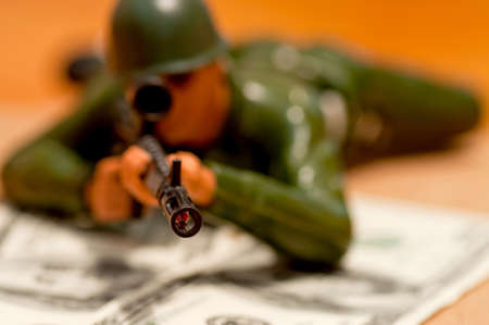 Plastic toy soldier on the hundred-Dollars banknotes (focus on the tube)  photo