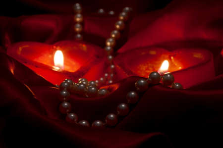 Pearls necklace and two burning heart-shape candles on the red satin photo