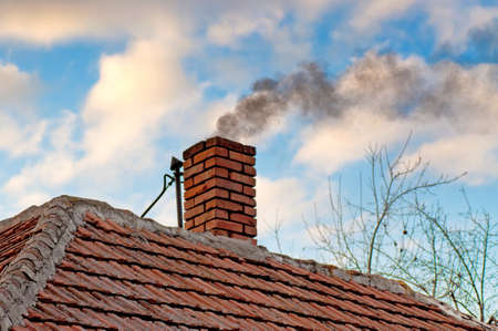 cope: Smoke from the chimney on the roof of the old house
