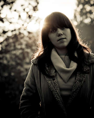 18's: Young brunette in the jacket with sun rays and tree branches in the background