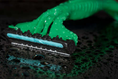 Close-up of a male razor on the black background with reflection and waterdrops photo