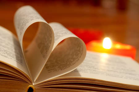 Close-up of book pages folded into a heart shape and burning heart-shape candle photo