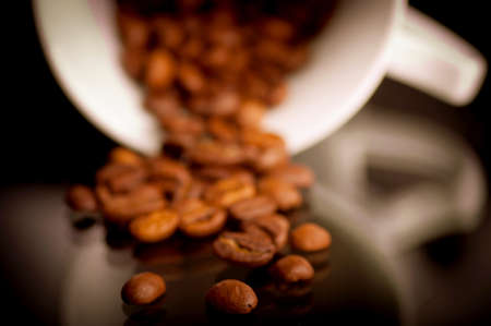 Macro shot of coffee beans from coffee cup on the reflective black background photo
