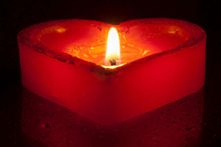 Burning heart-shape candle on the reflective background with waterdrops Stock Photo