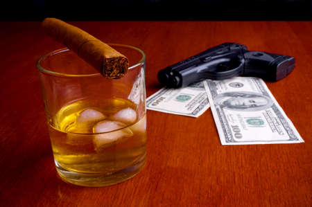 Cigar on the whiskey and two hundred Dollars bills under handgun photo