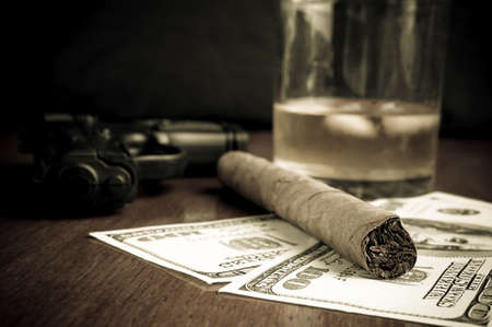 Cigar on the Dollars, handgun and whiskey in the background Stock Photo