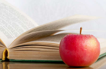 Wet red apple and book on the reflective surface photo