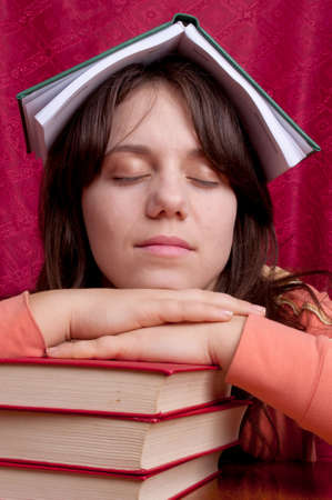 Teenage girl with a workbook on the head sleeping on a pile of books Stock Photo - 12312997