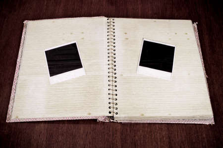 Two blank instant photo frames on the open old photo album photo