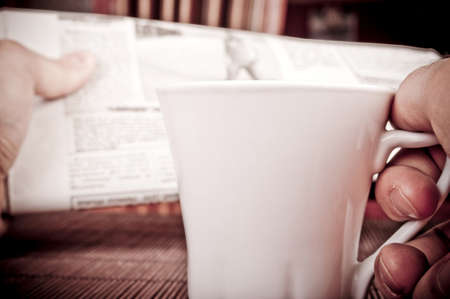 Male hand holding coffee cup in the right hand and blurred newspapers in the left hand Stock Photo - 12313125