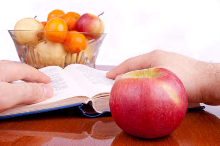 Student reading book and fresh apple in the front of the book, for a snack photo