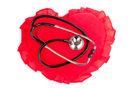 Stethoscope on the heart-shape pillow photo