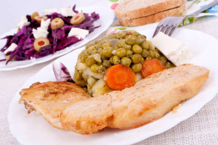 Roasted chicken breast with pea and red cabbage salad in the background