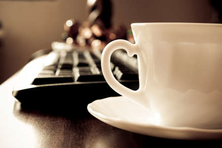 Coffee cup and blurred computer keyboard in the background Stock Photo
