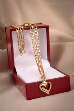 Golden necklace with heart-shape pendant in the box, on the beige silk photo