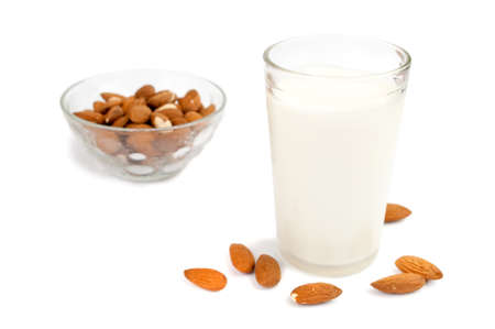 Glass of milk and few almonds around glass, bowl of almonds in the background