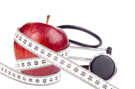 Fresh red apple wrapped with cntimeter tape and stethoscope isolated on white