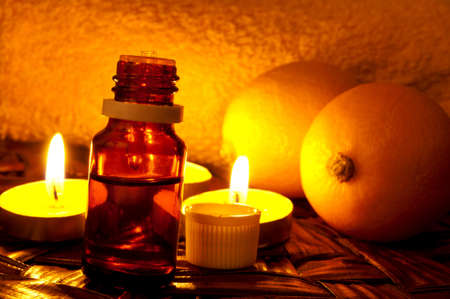 Bottle of lemon essential oil and candlelight photo