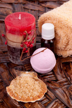 Fragrant sea salt, essential oil, soap and candle on the woven pad photo