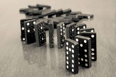 Dominoes in a row falling on the wooden table photo