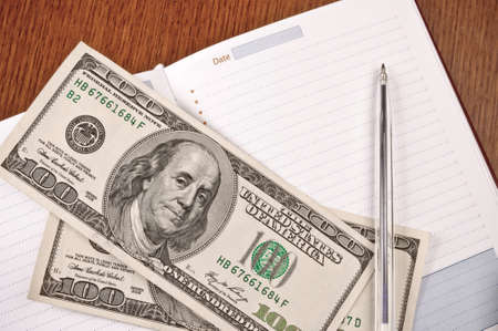 Blank page in the reminder, pen and two hundred-dollar bills photo