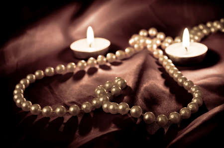 Heart shape made from pearls and two burning candleson the satin  photo