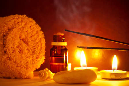 Smoke from scented sticks, towel, candles and essential oil bottle photo