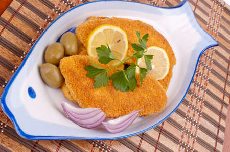 Breaded hake fillets in the fish-shape plate  photo
