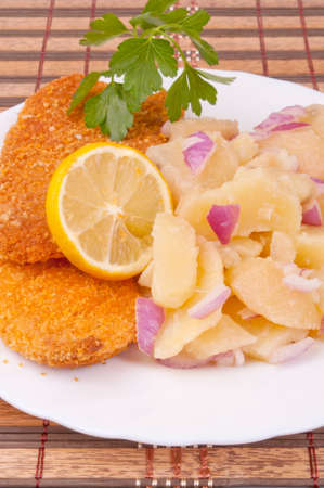 Breaded hake fillets and boiled potato salad with red onion photo