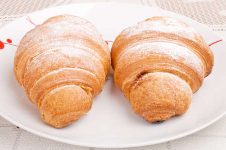 Croissants with powdered sugar on the plate photo