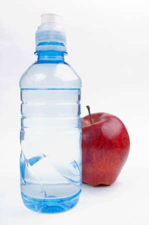 Bottle of water and red apple on white background photo