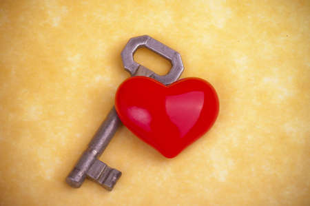 Old metal key and heart on the yellow background photo