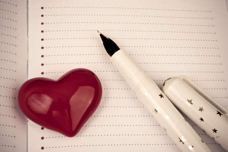 Decorative red heart and fountain pen on the blank page of notebook photo