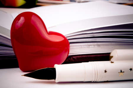 pad and pen: Decorative red heart and fountain pen next to the notebook Stock Photo