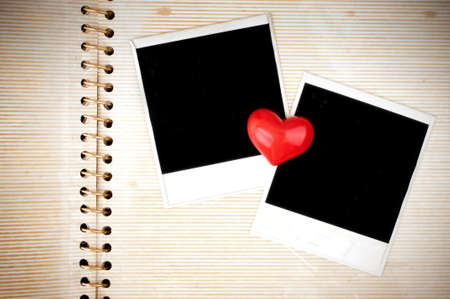 Two blank instant photo frames and heart on the old photo album page photo