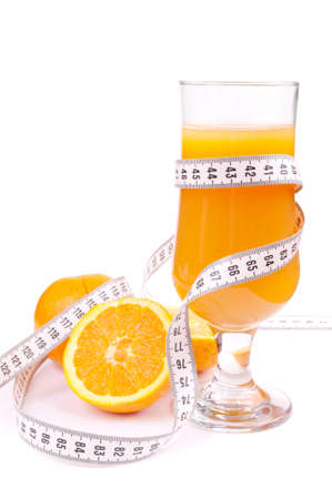 Glass of fresh orange juice, wrapped with centimeter and oranges isolated on white photo