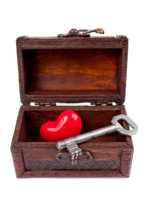 Old metal key and decorative heart in the wooden treasure chest, isolated on white
